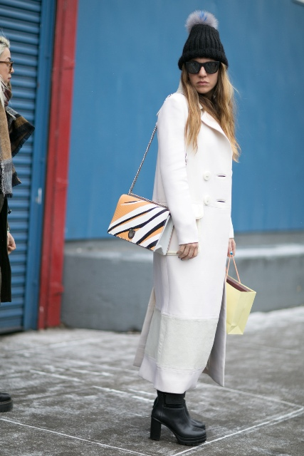 Czarna czapka z pomponem w innym odcieniu pasuje nawet do eleganckiego płaszcza do kostek
