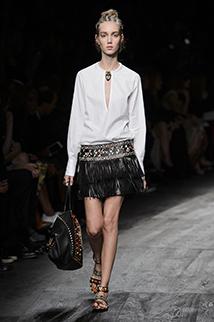 Biała bluzka połączona z czarną skórzaną spódnicą z frędzlami