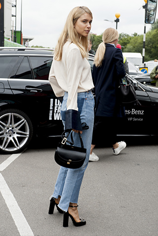 Biała elegancka koszula w połączeniu z jeansami o postrzępionych nogawkach